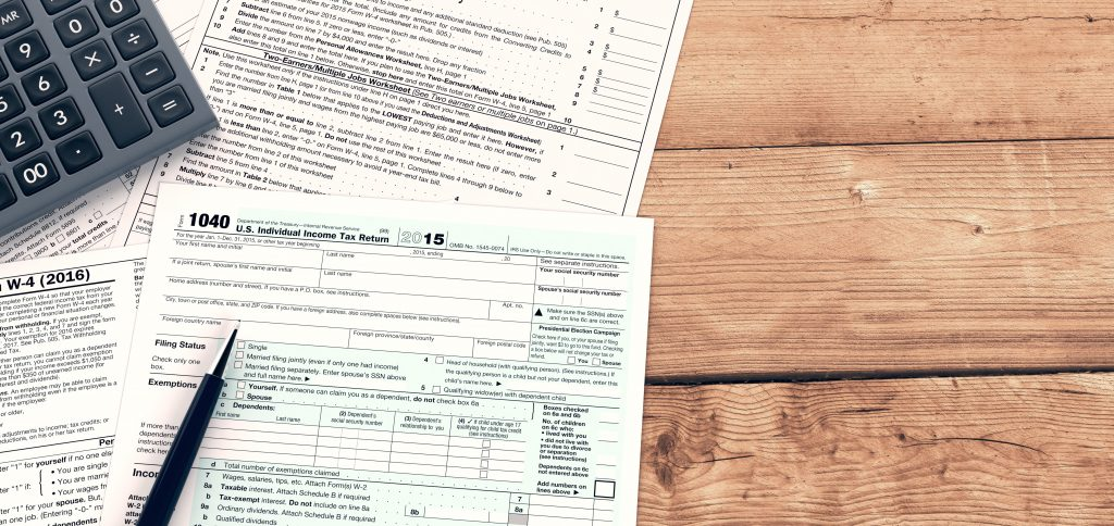 Tax forms, calculator and pen sitting on wooden desk